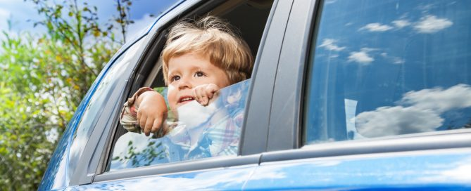 A little boy looks out the window of a car