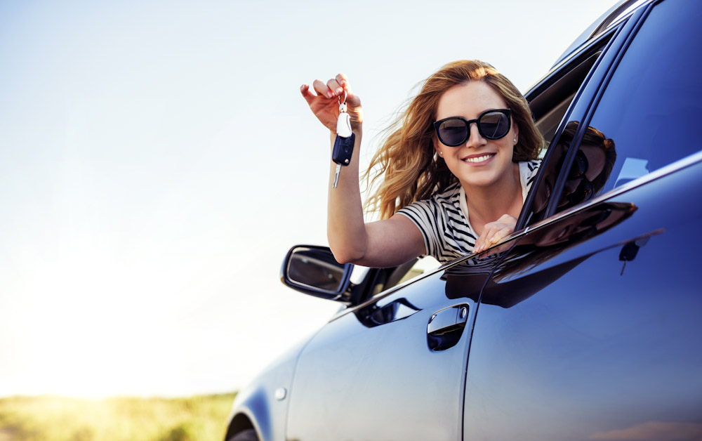 female peeking out her car window to show the keys of her brand new vehicle